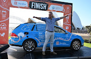 Dutch driver Wiebe Wakker celebrates in Sydney after complete a round-the-world trip with his retrofitted station wagon nicknamed The Blue Bandit.