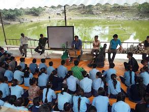 Photo: Children eagerly listen as the teacher plays the harmonium