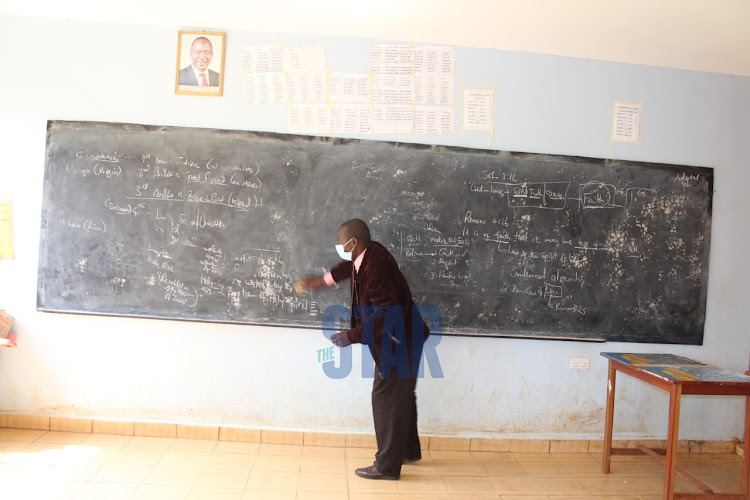 A teacher prepares an empty Standard 8 classroom at Kihumbuini Primary School, Kangemi on September 28, 2020