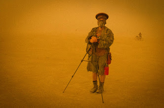 Photo: On one of the final afternoons, a bitter sandstorm blew across the playa. It was also the night of the big burn, so people began to amass near the man himself. I saw this fellow photographer setting up on the periphery, bracing himself against the storm. - from Trey Ratcliff at www.stuckincustoms.com