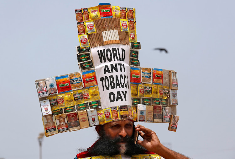 Social activist Rajendra Kumar Tiwari, wearing a headgear made from empty cigarettes packets, speaks on his cellphone as he conducts an anti-tobacco awareness campaign to mark World No Tobacco Day in Mumbai.