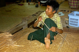 Photo: This young man uses a hatchet to break a little piece of bamboo off.  He holds the thin end between his toes and then pulls the small strip off.  The finished pieces are to the left.