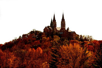 Photo: Church high on a hill with multiple steeples bright orange and golden Fall color woods.