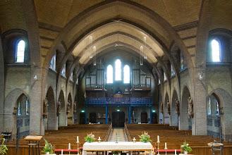 Photo: Het orgel achterin de kerk stamt uit 1931 en is gebouwd door Pels.  Eennieuw altaarwerd geschonken door de parochianen in 1974, bij het 50 jarig bestaan van de kerk. Het is een ontwerp van Jaap Min. Het smeedwerk is uitgevoerd door Hillebrand Hoebe en het houten altaarblad is gemaakt door Jaap Hopman. In 1984 werd bij het 60 jarig bestaan de ambo geschonken uitgevoerd door dezelfde heren. Dit geldt ook voor de doopvont (rechts) en de Paaskaarskandelaar.  The organ in the back of the church was build in 1931 by Pels.  The altar was made by Fa. J.P. Maas en Zonen situated in the city of Haarlem. The altar is made from marble and yellow copper and was designed by Jaap Min.