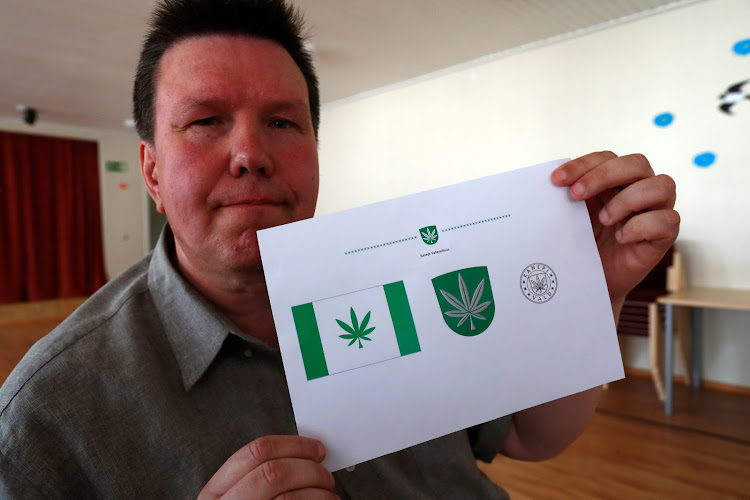 Designer Tonu Kukk holds a paper with a design of Kanepi municipality's flag and coat of arms featuring a cannabis leaf after the municipality council's vote in Polgaste, Estonia May 15, 2018. Kanep is the Estonian word for cannabis.