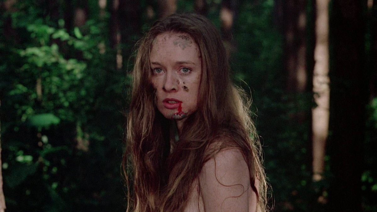 Camille Keaton in I Spit On Your Grave. Jennifer stands naked in a forest, with mud and blood smeared on her face, her long brown hair hanging down in a tangled mess. She looks towards the camera, slightly fearful.