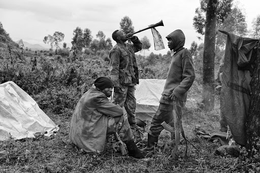 A Congolese soldier blows a South African vuvuzela to summon his comrades for a church service close to the frontline during the Battle of Kibati near Goma in the Democratic Republic of Congo.