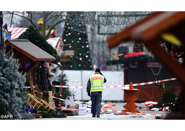 A policeman walks at the Christmas market in Berlin the day after a terror attack   - AFP