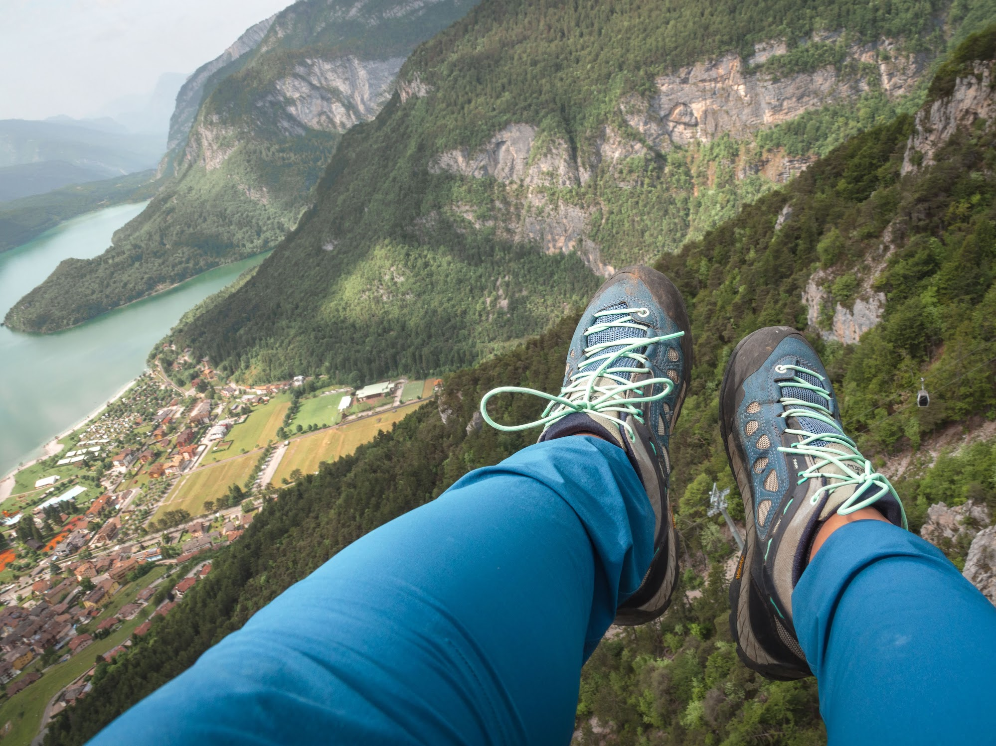 My legs high above Lake Molveno during paragliding in the Dolomites