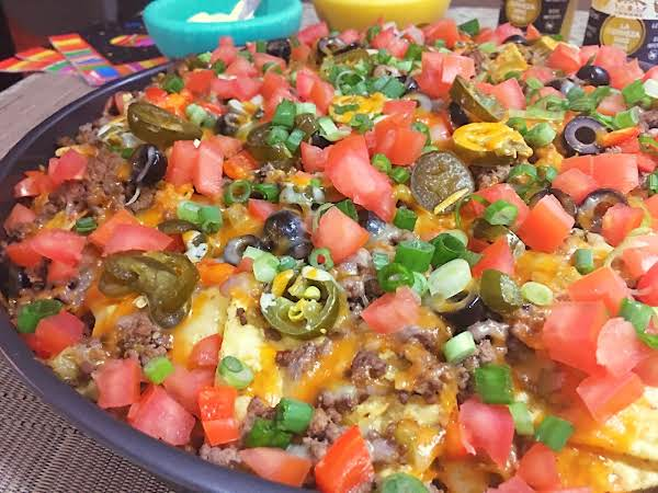 Nacho On A Plate With Turquoise Bowl In The Background.
