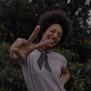 Woman outside, wearing scarf around her neck, and posing with her fingers in a peace sign