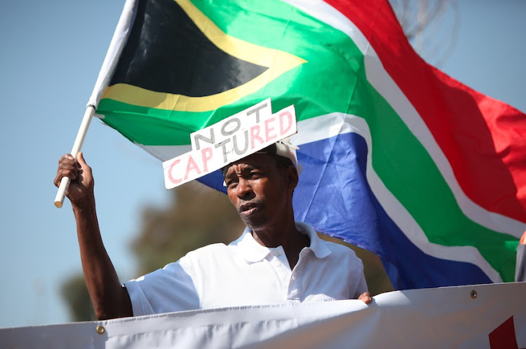 Ali Gule from NPO, Organisation Undoing Tax Abuse (Outa) holds a flag during a picket, 20 August 2018, outside the State Capture Inquiry in Parktown, Johannesburg.