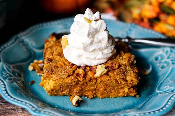 A Piece Of Pumpkin Cobbler On A Plate With Whipped Cream.