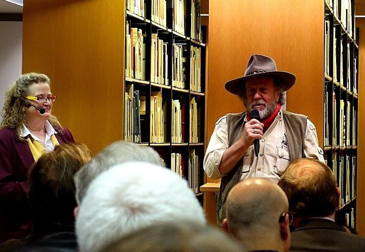 Das Foto zeigt den Künstler Gunter Demnig bei seiner Ansprache anlässlich der Eröffnung, links neben ihm Dr. Elke Purpus, Direktorin der Kunst- und Museumsbibliothek