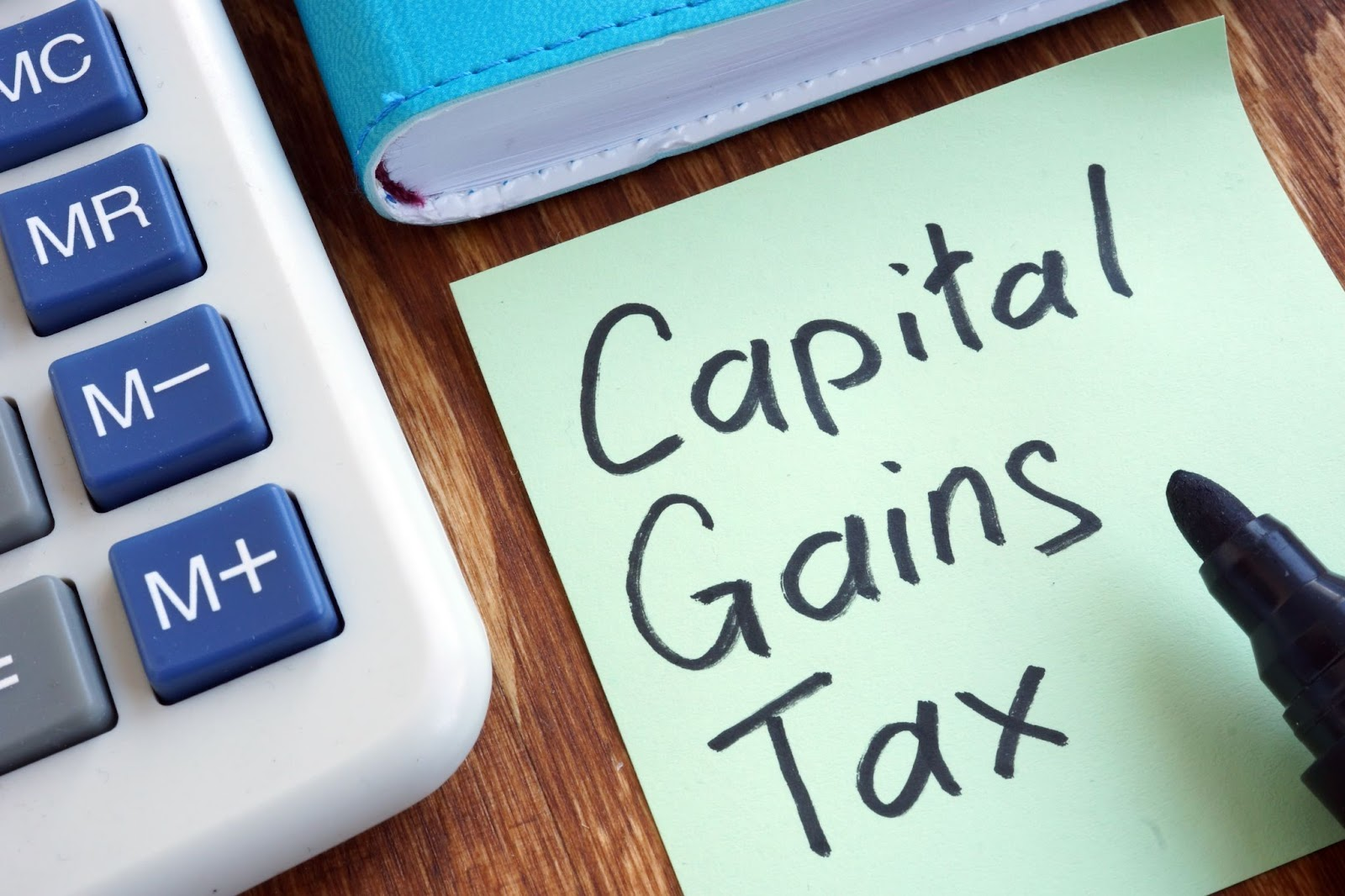 Capital, Gains, Tax written in a sticky paper and a calculator