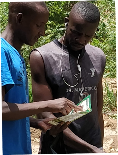 Two men reviewing a document while standing in a smallholder farm.