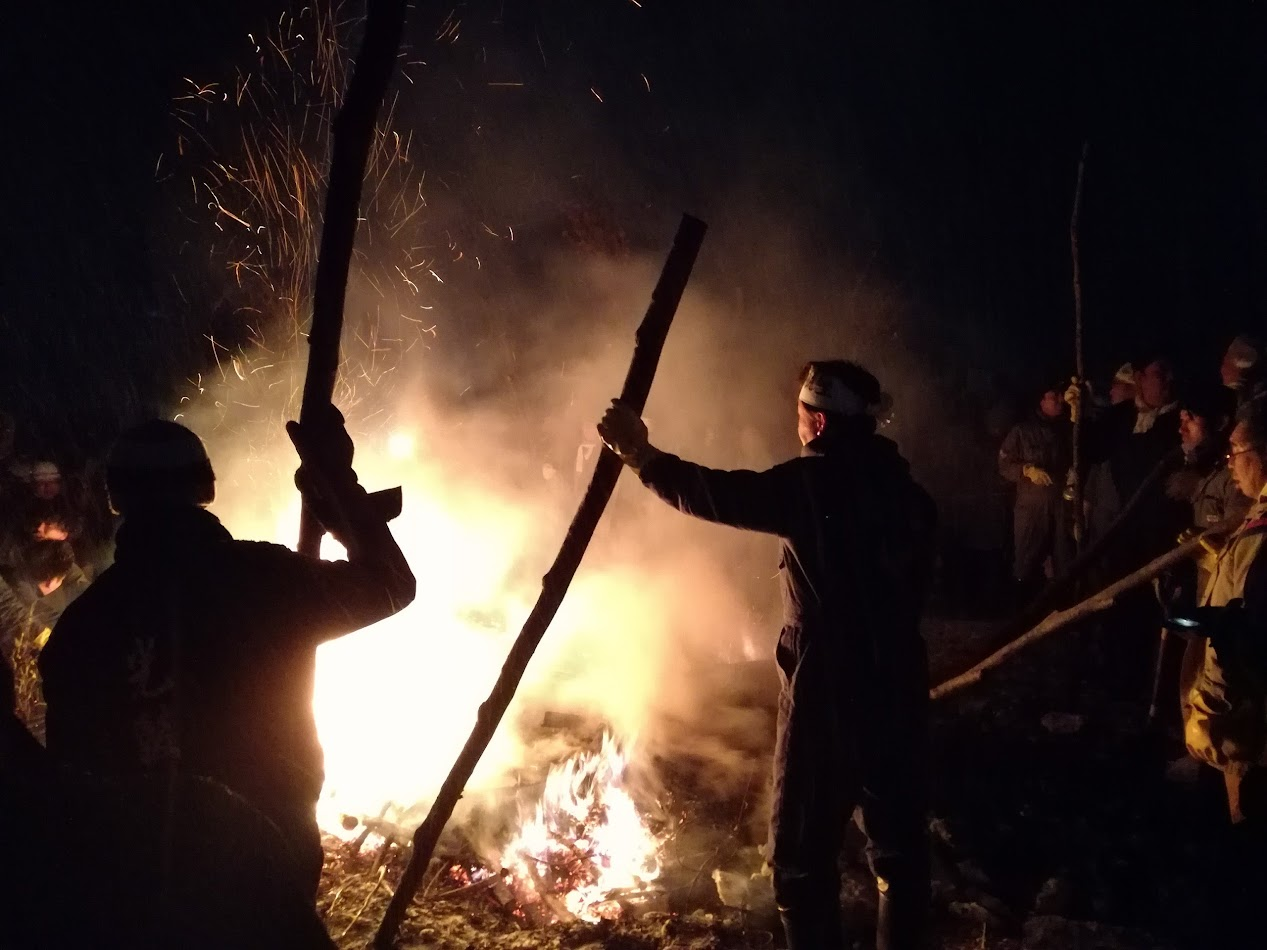 Taking turns to stoke the bonfire.