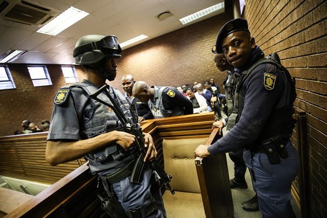 Members of the Tactical Response Team at the in the Roodepoort Magistrates court in the West Rand, Johannesburg monitor the court rooms where four men are appearing in connection with a cash in transit heist, one of them a former ANC Luthuli House employee, 31 July 2018