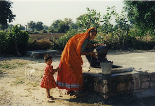 Photo: Village woman and child  drawing water