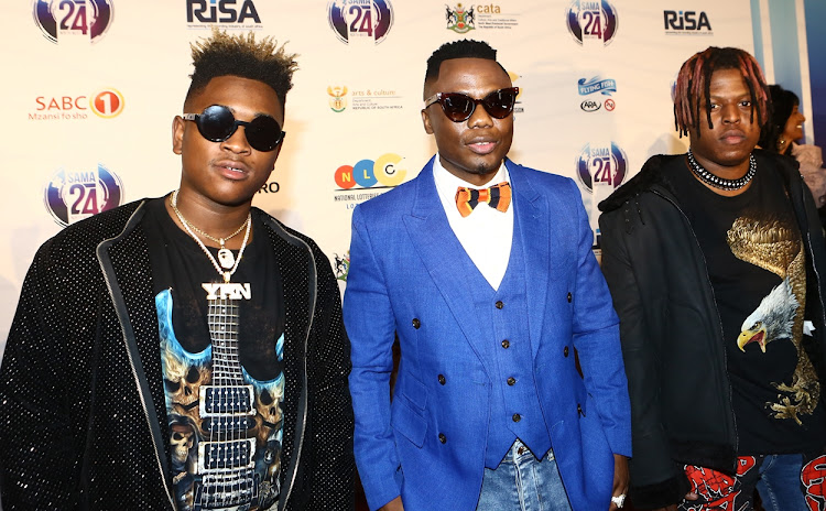 Dj Tira, flanked by members of the Destruction Boyz, on the red carpet before the start of the 2018 South African Music Awards.