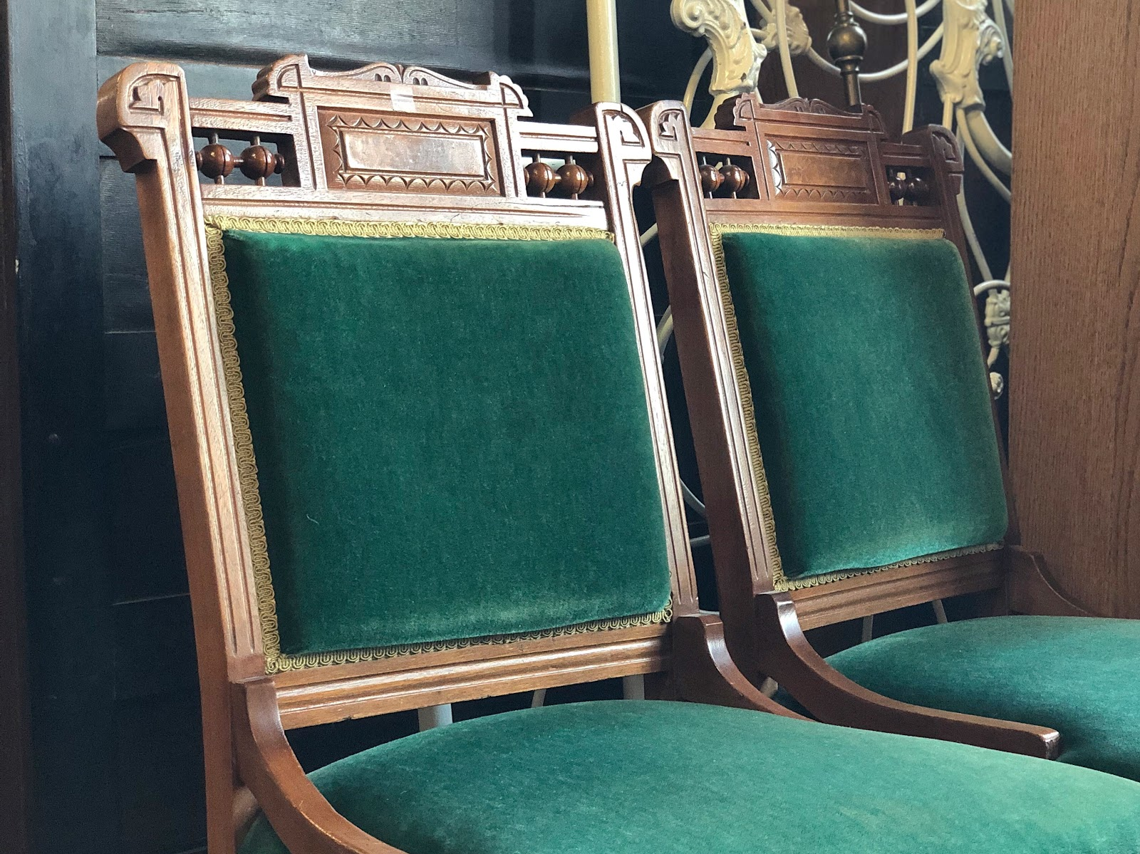 Two timeless chairs made out of wood and green fabric used as an eco-friendly furniture choice.