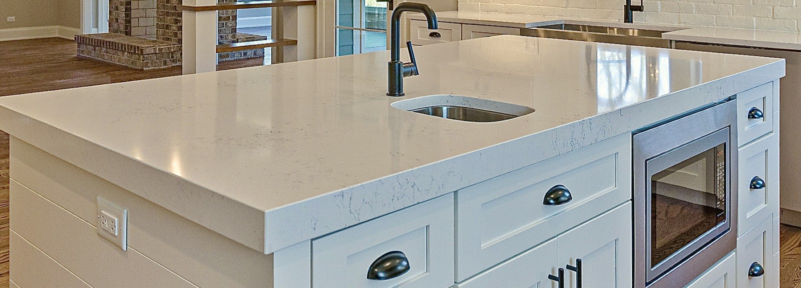 Close up of a quartz countertop with marble veining  on an kitchen island. Featuring a prep sink and stainless steel microwave drawer and dark hardware to contrast the white cabinets.