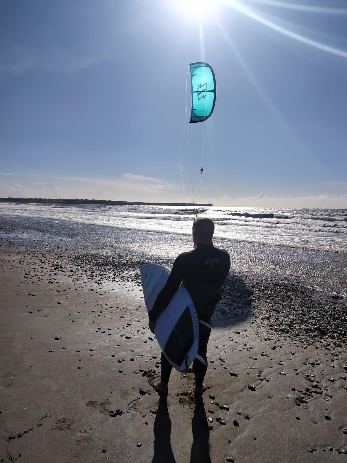 Un hombre caminando en la playa  Descripción generada automáticamente