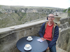 Photo: Chris having a cappuccino. The cliff that Matera sits on overlooks a ravine; on the other side of the ravine is another cliff, also with a lot of caves (and cave dwellings) in it. That cliff is now a national park and does not have any inhabitants.