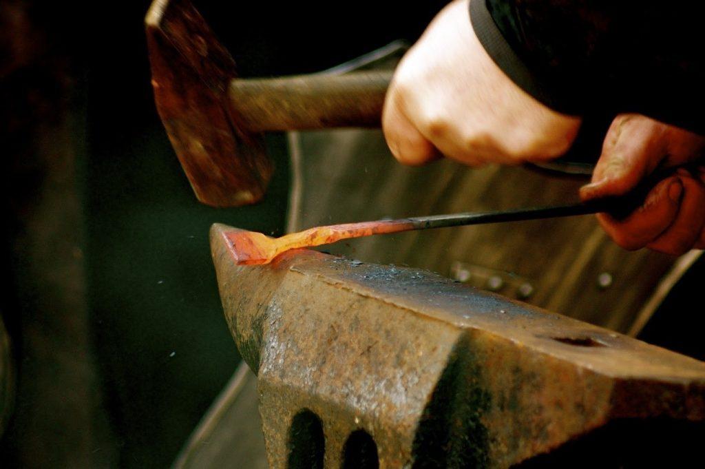 Conformação de Peça de ferro em alta temperatura sendo martelada, processo conhecido como Forjamento.