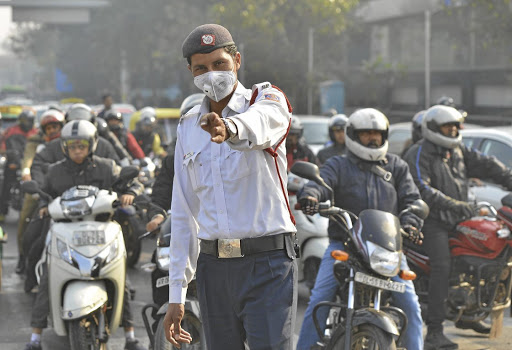 A traffic policeman wears a face mask to protect himself against pollution in New Delhi. Picture: GETTY IMAGES