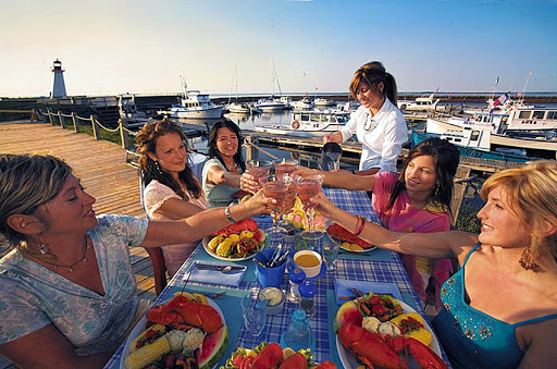 Women toast a sunny day and seafood feast in Shippagan, New Brunswick, Canada.