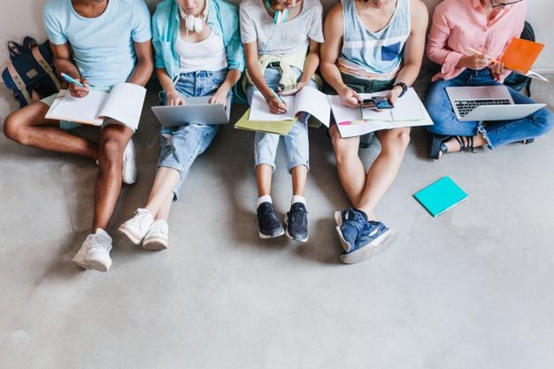 Retrato de alunos de tênis da moda relaxando no chão enquanto se preparavam para os exames. amigos da universidade passando um tempo juntos usando laptops e escrevendo resumos. Foto gratuita