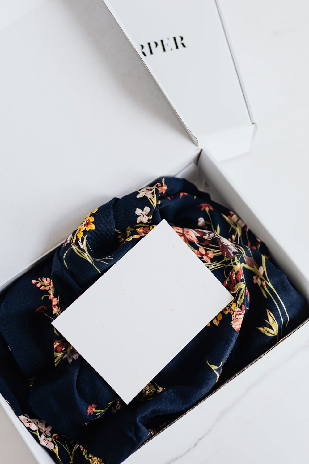 A post card on top of clothing in a branded shipping box