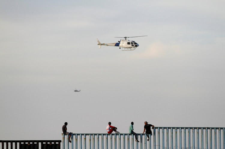 Migrants sit on top of the border fence between Mexico and the US.