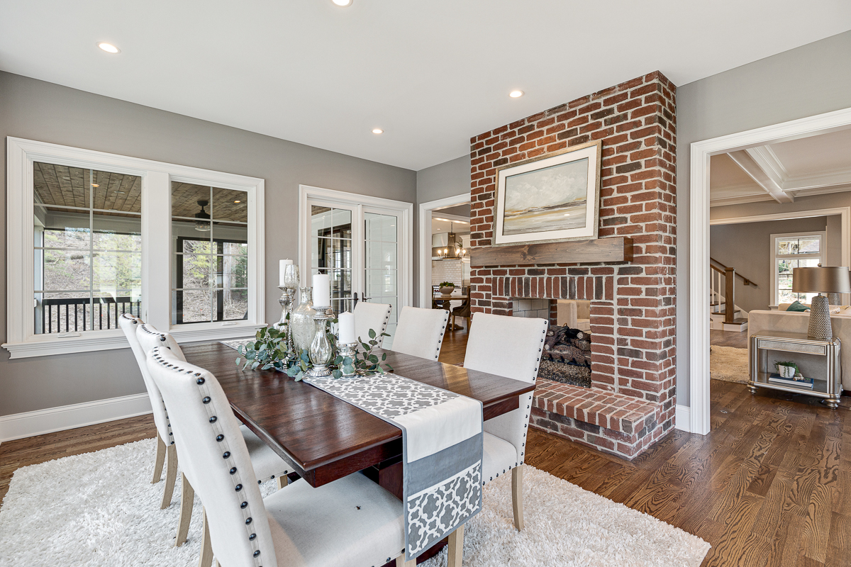 Pass through fireplace dining room with natural light, wood and brick elements and a neutral color palette.