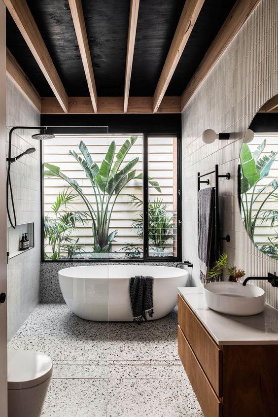 Banheiro bem iluminado enfeitado com plantas e uma banheira pequena