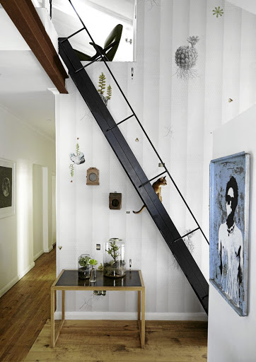 The  steel ship-style ladder was made to order and leads to a mezzanine where the couple can work (or play TV games!) The wallpaper  is by Nina's design company Room 13 Collection.