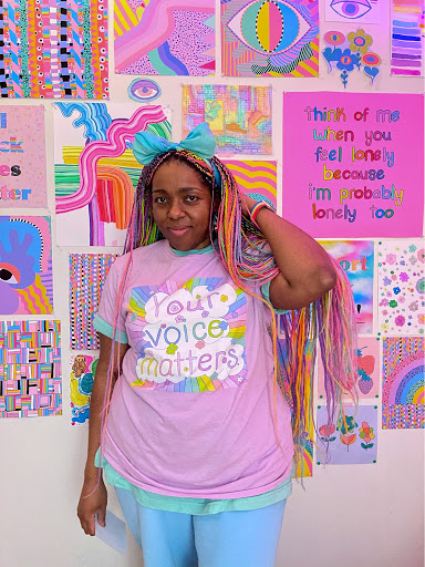 Artist with rainbow colored individual braids standing in front of their rainbow colored artwork.
