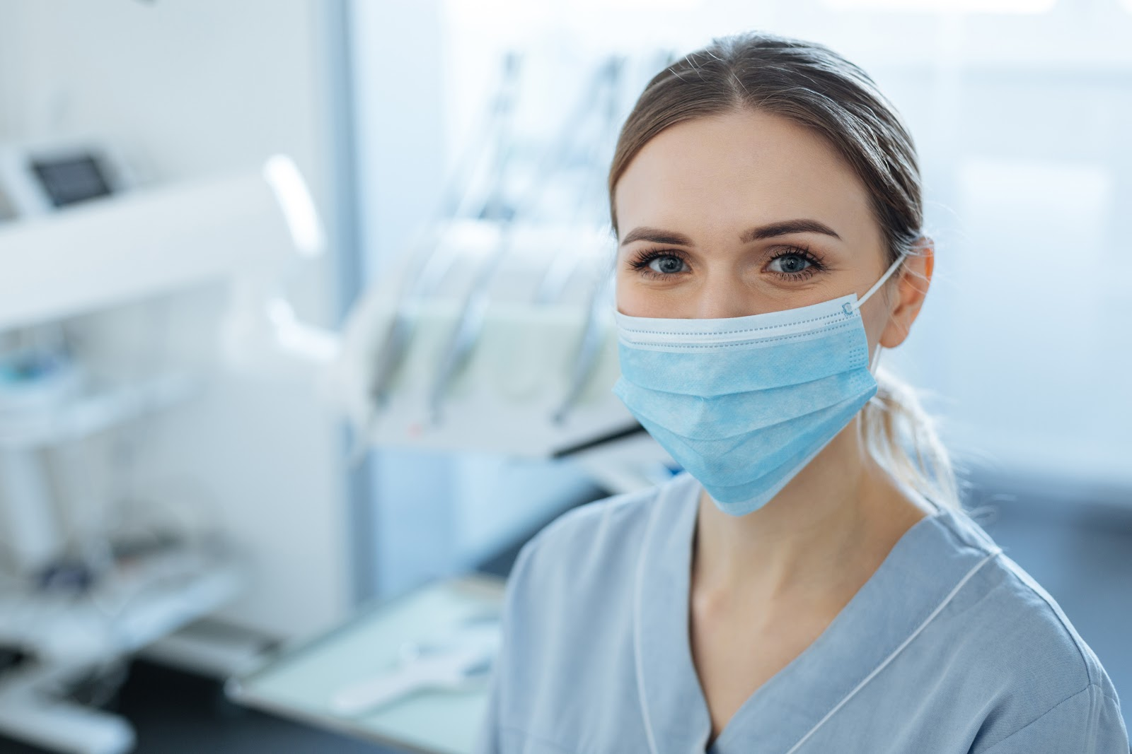 Cheerful young female dentist wearing a face mask
