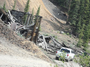 Photo: Part of the mining operation falling apart.  Note the orange talus slope in the background - part of the mine tailings associated with gold mining.