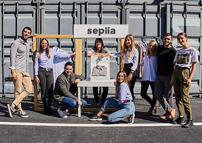 The team of Sepiia pose in front of their sign outside.