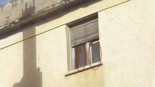 Mujer posando en una foto y un fantasma aparece en la ventana