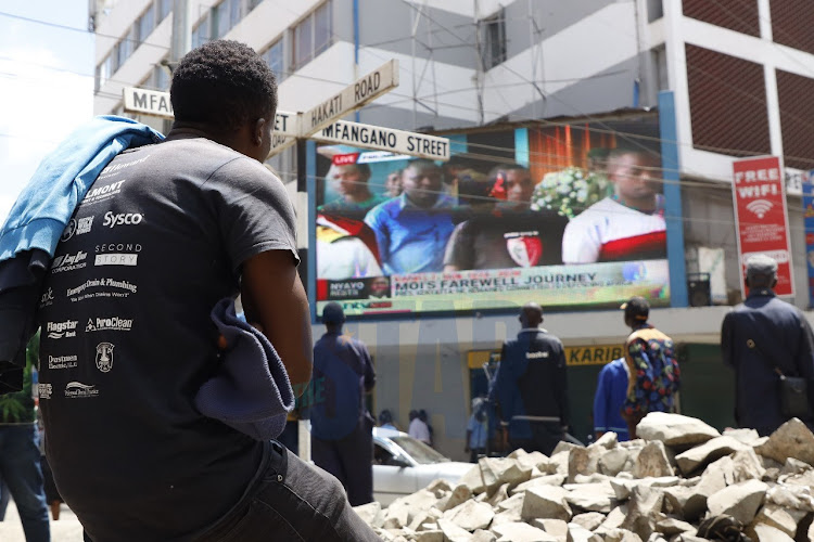 A Kenyan follows the proceedings of the viewing of former President Daniel Moi's body.