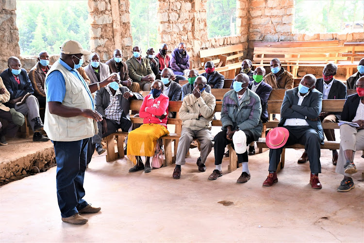 Kenya Water Towers Agency acting director general Julius Tanui engages the community during the handing over of the fencing site officially to the contractor at Maasai Mau.