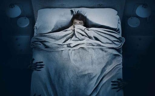 Mujer atormentada por sombras en la noche