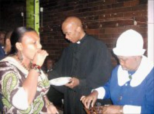 COVENANT: Resident priest of the KwaThema Central Methodist Church in Springs, Revered Smadz Matsepe, adminidters Holy Communion to members of his congregation during the 2008 Covenant Service yesterday. Pic. Dan Fuphe. 20/01/2008. © Sowetan.