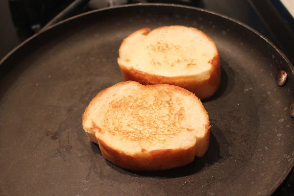 Wipe pan clean and toast slices of French bread in pan.