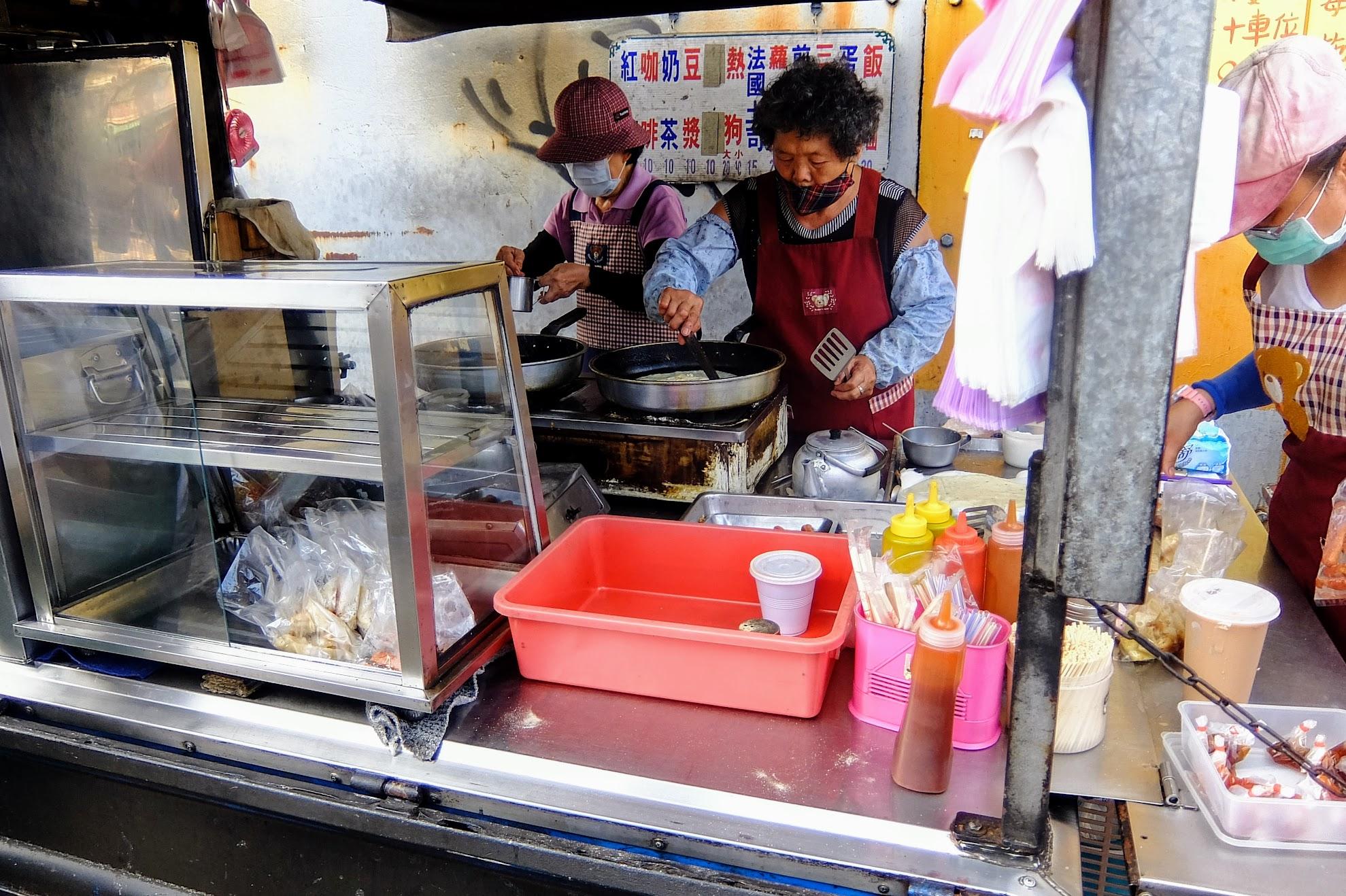 人手頗多,但還是應付不及來買的客人,生意真的不賴! 在這照片可以看到二鍋正在弄蛋餅,後頭還有一個人在處理蛋餅和煎餃,只是都來不及賣....