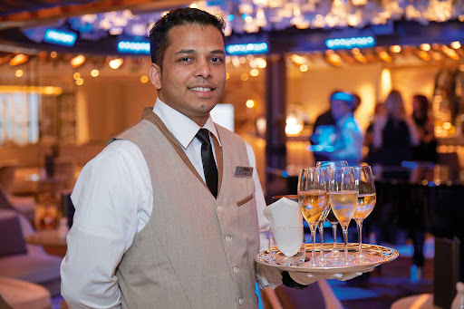 A member of the wait staff pauses at the Constellation Theater aboard Seven Seas Splendor.