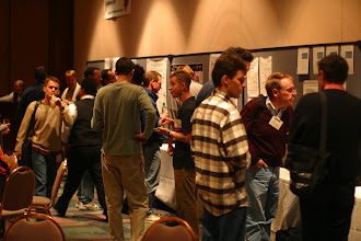 Photo: Busy post sessions at the evening reception, EclipseCon 2004.  John Arthorne and Darin Swanson chat.